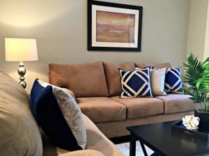 Fully furnished apartment with tan couches and black coffee table