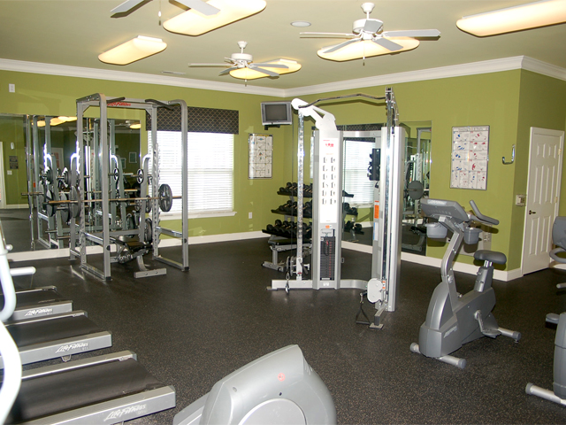 Fitness room with cardio equipment, cable machine, free weights, and a barbell rack