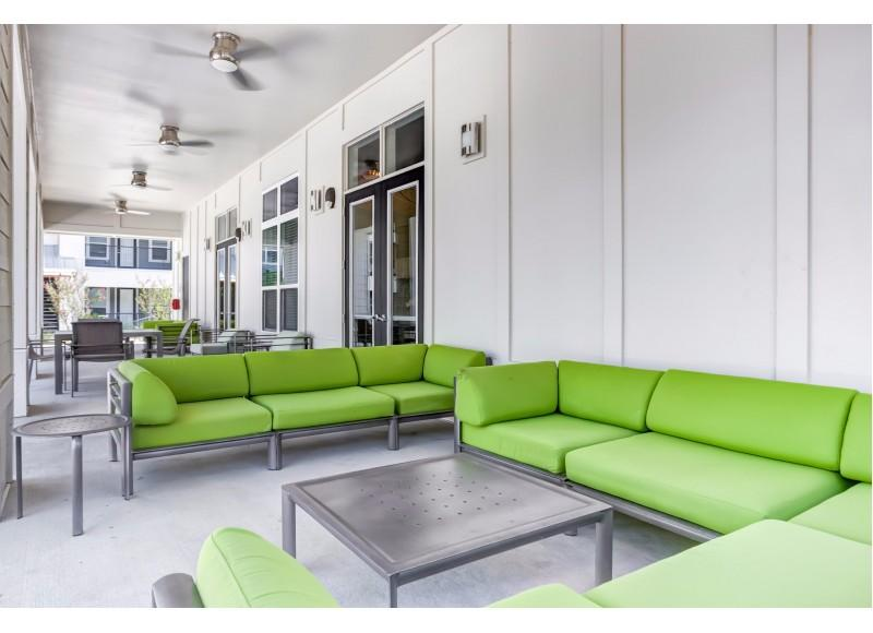 Patio area with bright green furniture and dark gray tables