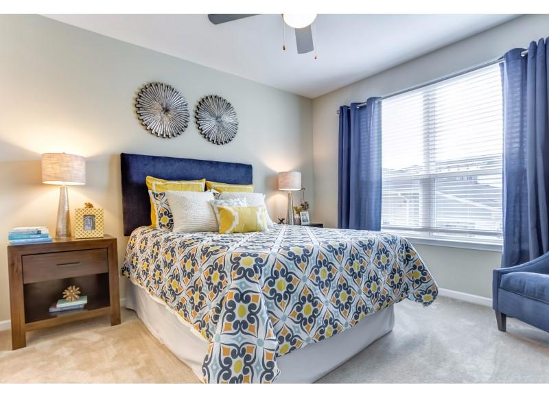 Furnished bedroom with a yellow and blue comforter, blue curtains, and carpet flooring.