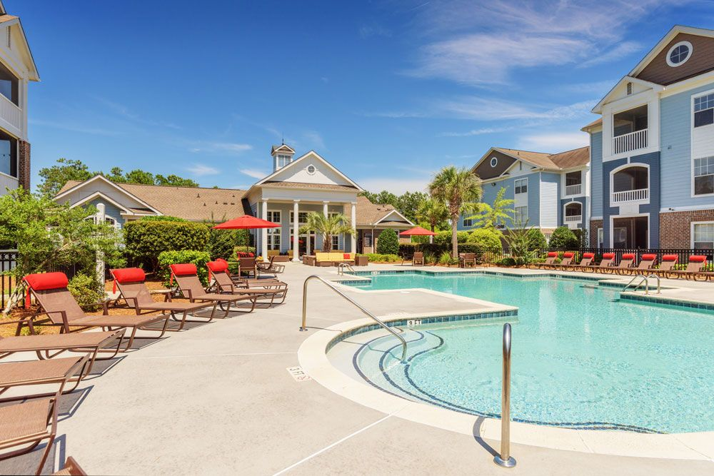 Outdoor pool and clubhouse with lounge chairs at Vista Sands corporate rentals